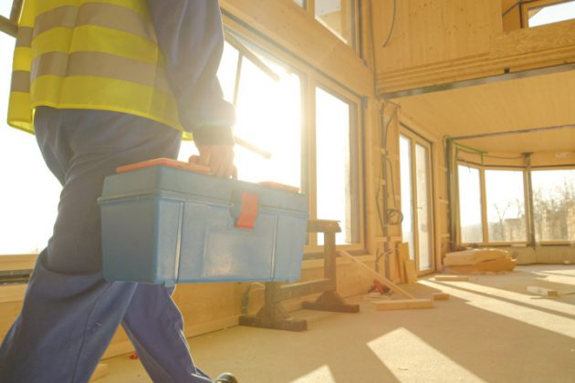 A construction worker walks with a tool box in a retrofit construction project